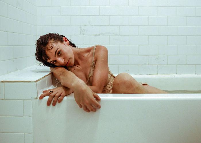 Portrait of woman sitting in bathtub