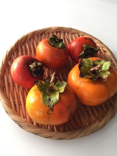 Persimmons on wicker plate