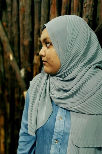 Young woman wearing hijab looking away outdoors
