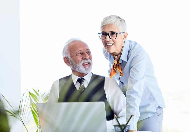 Senior businessman looking smiling colleague standing by laptop on table