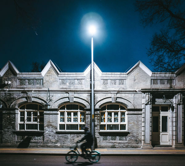 Bicycle by building against sky at night