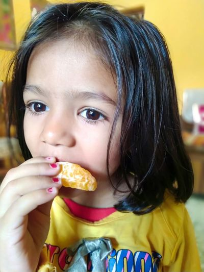 Orange - Fruit Child Portrait Childhood Eating Girls Headshot Looking At Camera Cold Temperature Front View Close-up Frozen Food Eye Color Temptation Finger In Mouth Brown Eyes Babyhood One Baby Girl Only