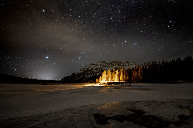 Night shot mountain, lit trees and frozen lake, banf