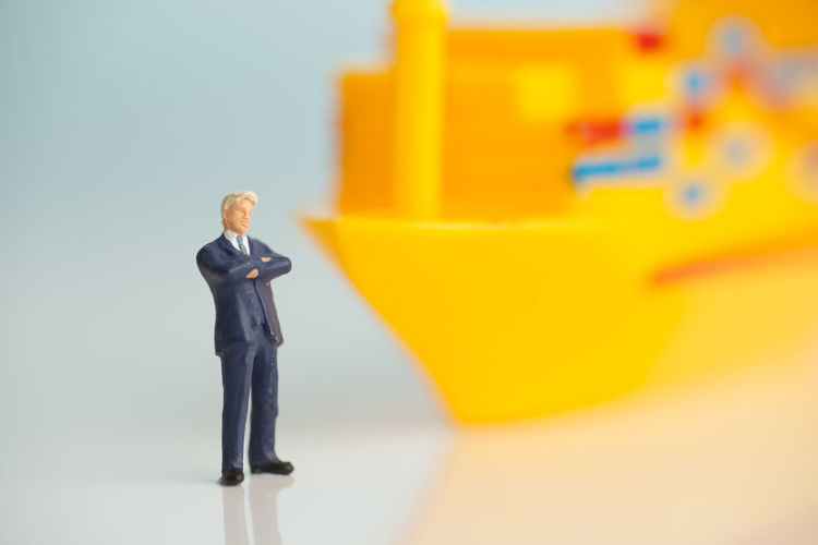 Miniature figures of a successful businessman with shipping background. Business Economy Industry Leader Logistics Transportation Business Business Person Businessman Cargo Cargo Container Commercial Concept Corporation Freight Transportation Magnate Miniature Ship Shipping  Success Successful Suit Traveller Tycoon Well-dressed