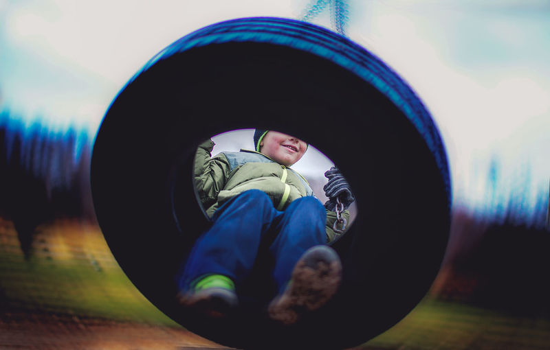 Close-up view of boy on swing