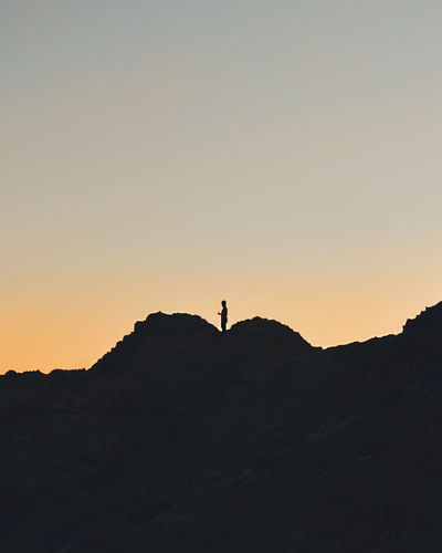 SILHOUETTE OF PERSON STANDING ON HILL AT SUNSET