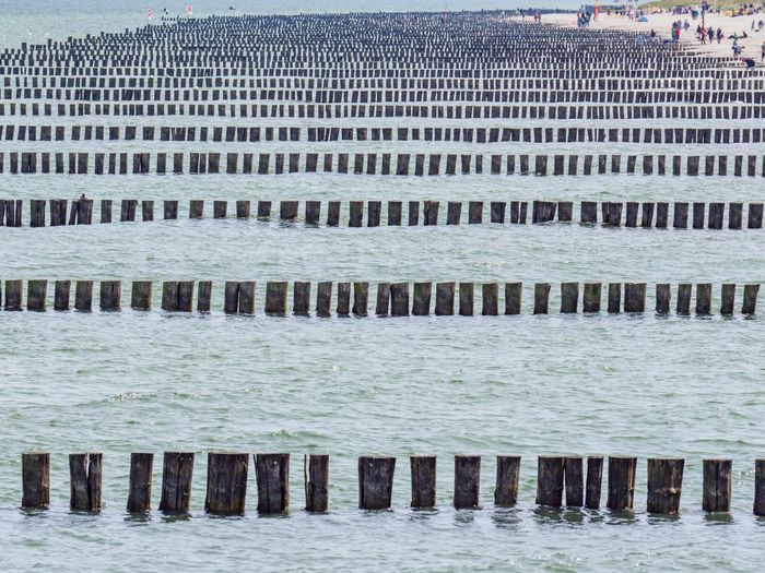 Wooden posts on sea against buildings in city