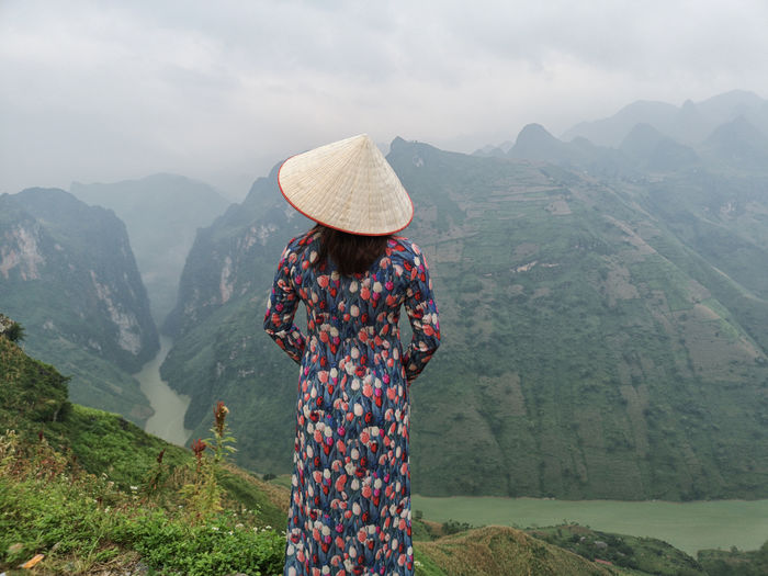 Rear view of woman wearing asian style conical hat looking at mountains