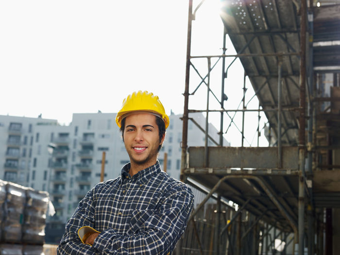 Portrait of young man standing against built structure