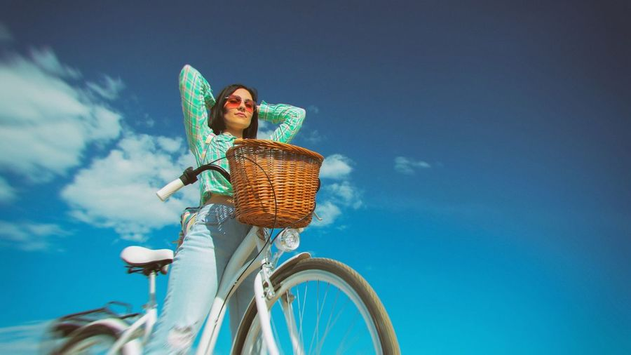 Low angle view of young woman with bicycle against sky