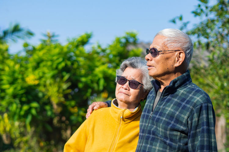 Portrait of an elderly couple smiling and looking away while standing in a garden