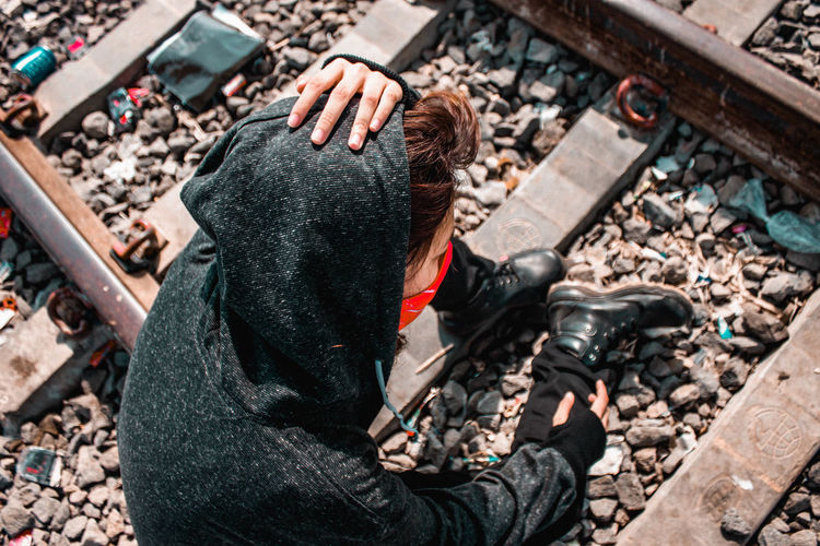 High angle view of woman sitting on railroad tracks