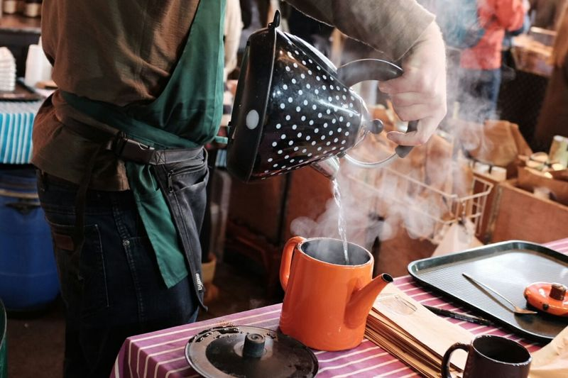 Midsection of man pouring boiling water from kettle at borough market