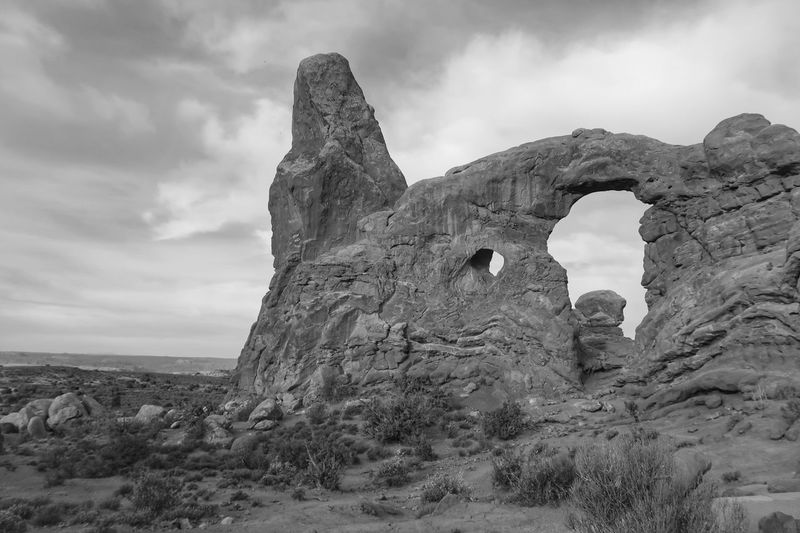 Black and white landscape of rock formation with windows and a chimney