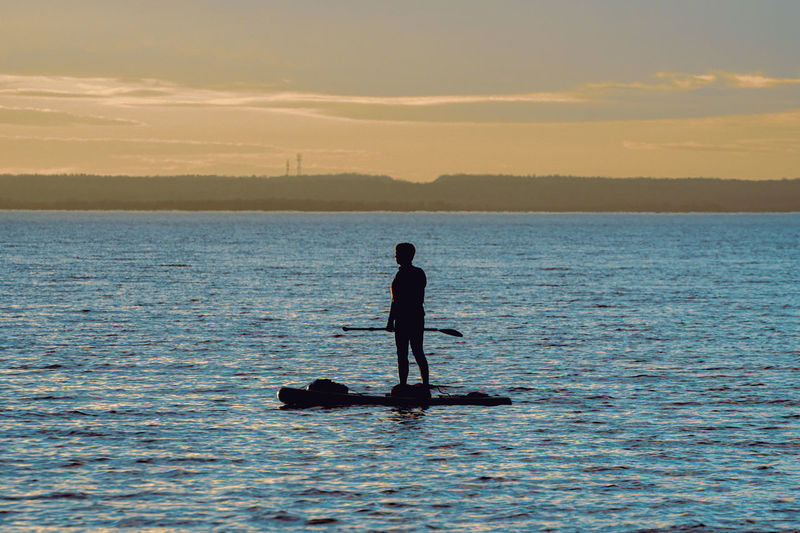 Silhouette man rowing boat against sky during sunset