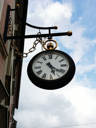 Low angle view of old clock on building against sky