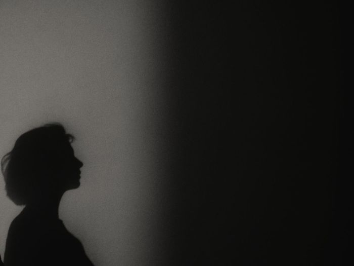 Side view of silhouette woman standing against wall