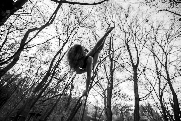 Low angle view of woman pole dancing against bare trees in forest