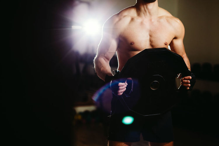 Midsection Of Shirtless Muscular Man Lifting Weights While Standing In Gym
