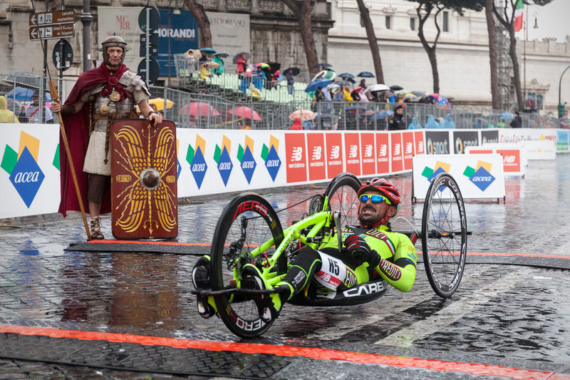 Rome, Italy - March 22, 2015: 21 Rome Marathon, the athlete Giagnoni Christian comes fifth at the finish line in the race hand bikes. Athlete Atletic Bycicle Competition Day Fatigue  Gladiator Hand-bikes Handbike  Handicap Italy Marathon Outdoors Rain Road Rome Runners Running Street Running Three-wheeled Bicycle Water Weel Chairs