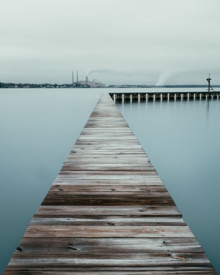 Wooden pier on jetty against sky