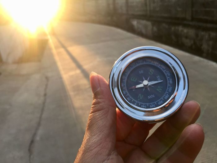 Compass Human Hand Hand Holding Human Body Part Direction One Person Real People Finger Guidance Navigational Compass Human Finger Focus On Foreground Sunlight Day Body Part Accuracy Outdoors Unrecognizable Person Close-up