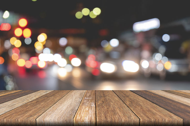Defocused image of illuminated lights on table in city at night