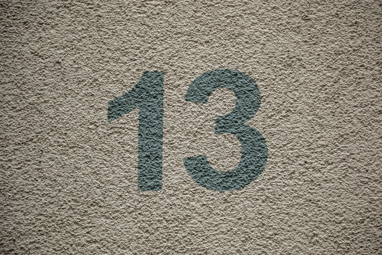 Number 13 of the house with green letters No People Textured  Day Sign Close-up Communication Outdoors High Angle View Asphalt Rough Number Road Paint Sand Black Color Wall - Building Feature Pattern Directly Above Full Frame Symbol
