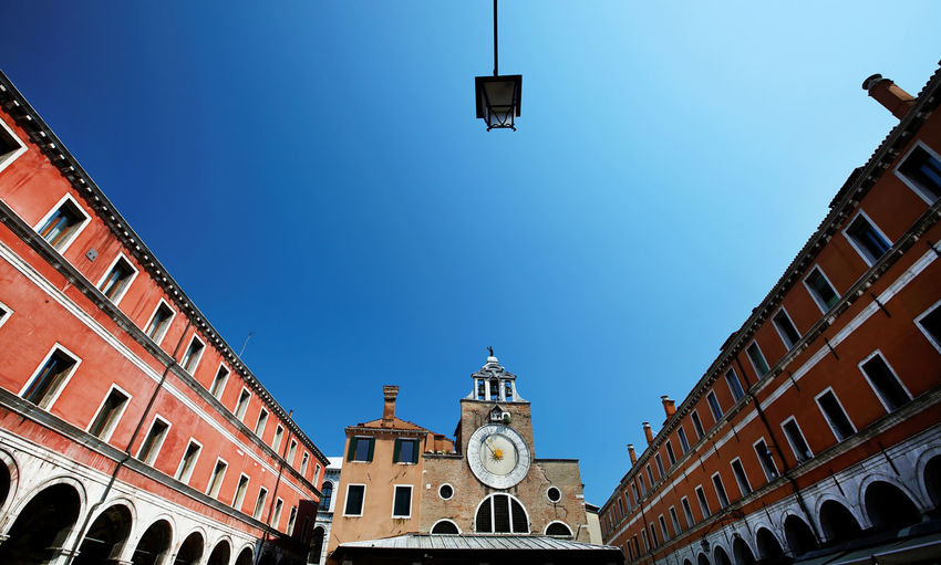 Low angle view of san giacomo di rialto at town square against clear blue sky