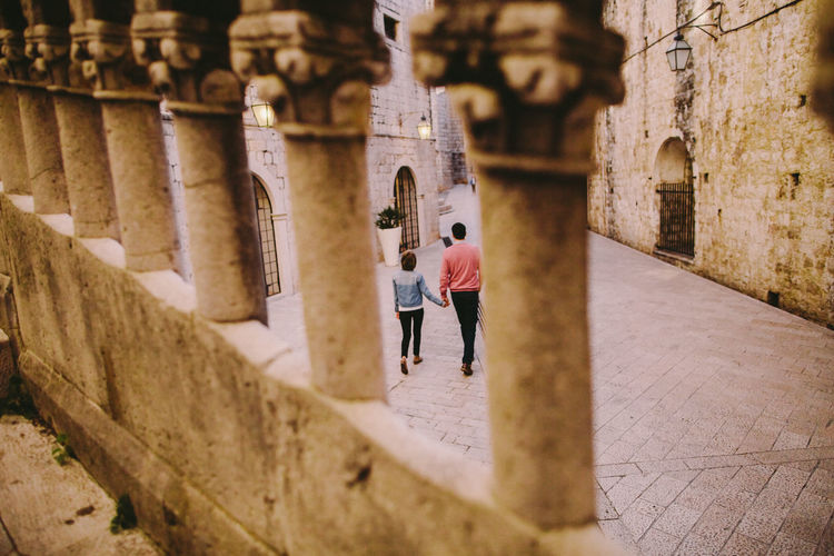 Rear View Of Couple Walking On Footpath Seen Through Railing