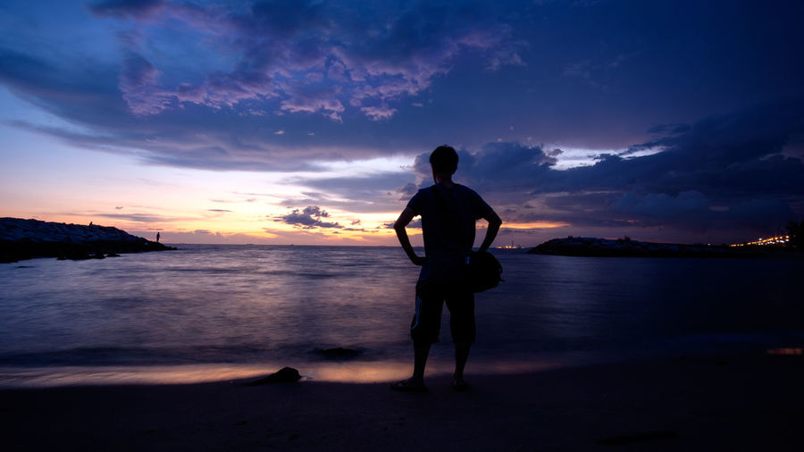 Scenic View Of Man At Beach At Sunset
