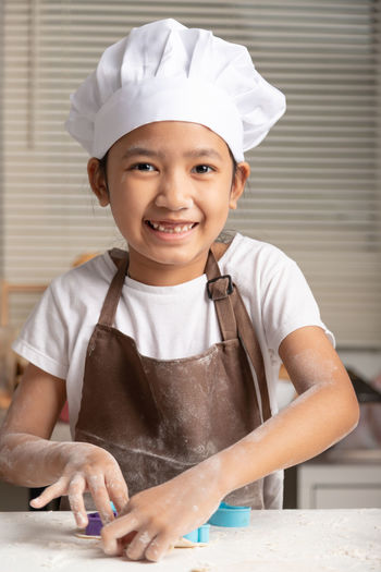 The little girl wore a white chef hat and a brown apron. the kid making cookies in the kitchen.