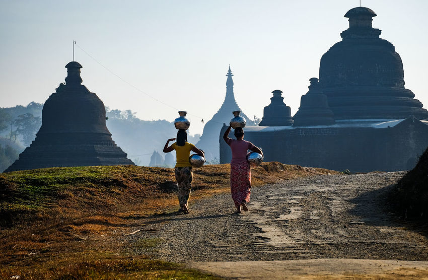 Two girls carrying jar on the way to temple Carrying Mrauk-U Rakhine State Architecture Countryside Culture And Tradition Day Full Length Harvest Human Representation Nature Outdoor Outdoors Pagoda Building People Real People Sculpture Sky Statue Travel Destinations Walking Women