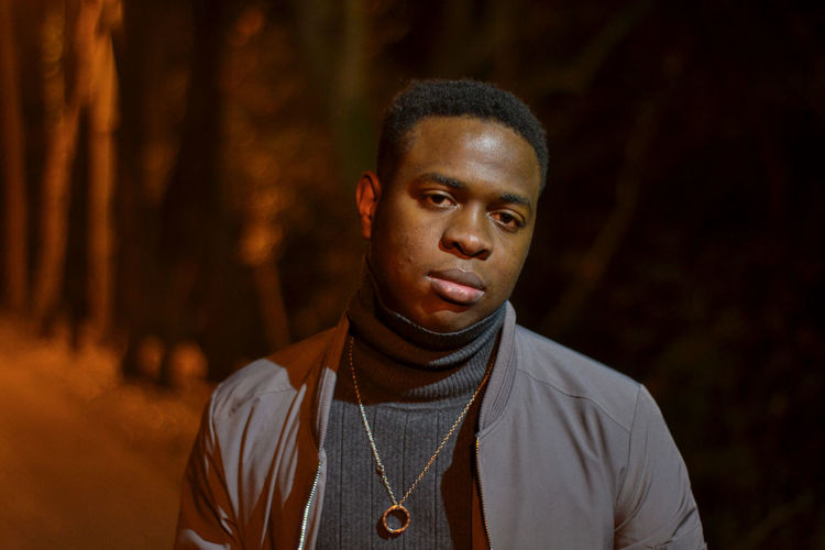 Portrait of serious young man standing outdoors at night