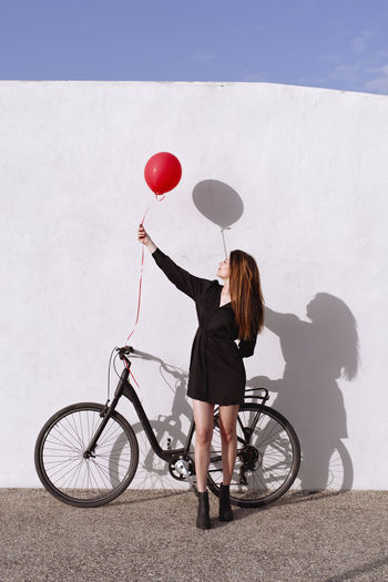 Full length of woman with bicycle standing against wall