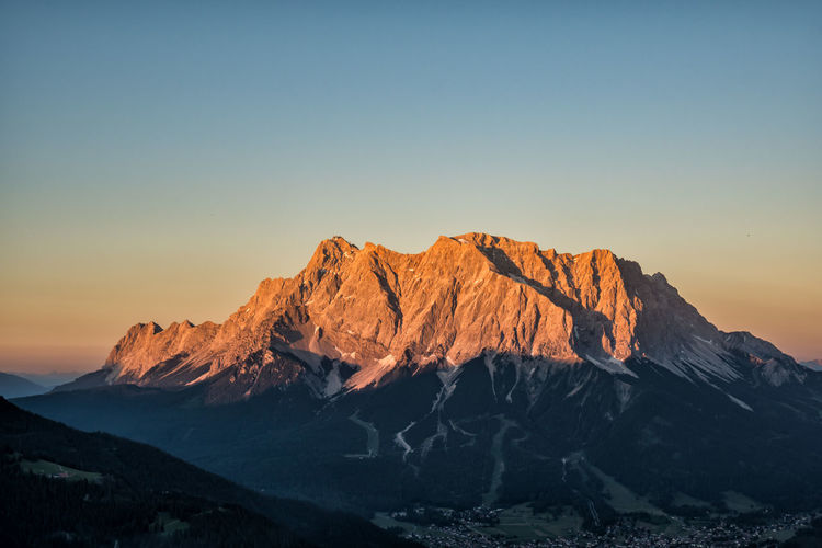 Zugspitze in sunset The Great Outdoors - 2019 EyeEm Awards Zugspitze Tyrol Austria Alps Arid Climate Mountain Peak Snowcapped Mountain Formation Outdoors Geology Remote Orange Color Mountain Range Rock No People Landscape Environment Non-urban Scene Copy Space Nature Idyllic Clear Sky Tranquility Tranquil Scene Sunset Beauty In Nature Mountain Scenics - Nature Sky Alpenglow