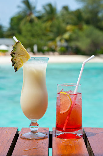 Close-up of drinks on wooden table against swimming pool
