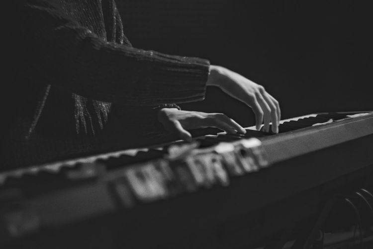 Midsection of woman playing keyboard