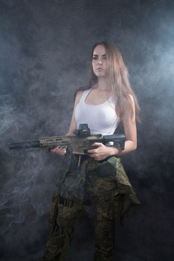 Adult Beautiful Woman Clothing Communication Government Gun Hair Hairstyle Holding Indoors  Long Hair One Person Portrait Real People Smoke - Physical Structure Standing Three Quarter Length Uniform Weapon Young Adult Young Women