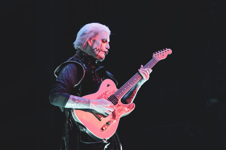 Midsection of man playing guitar against black background