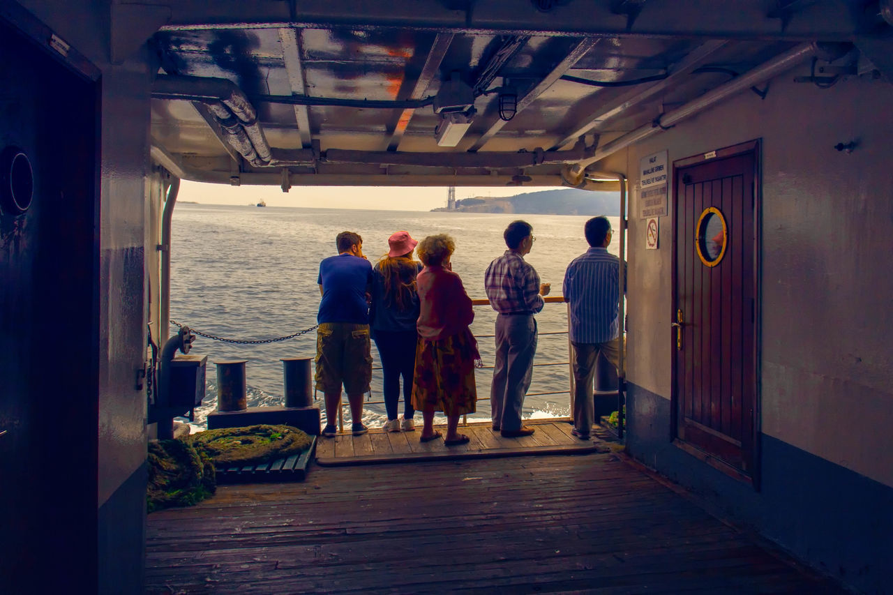 real people, rear view, men, medium group of people, full length, leisure activity, women, sea, lifestyles, indoors, nautical vessel, day, water, adult, people