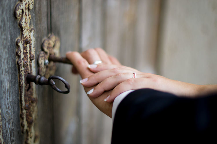 Cropped hands of couple holding key in door