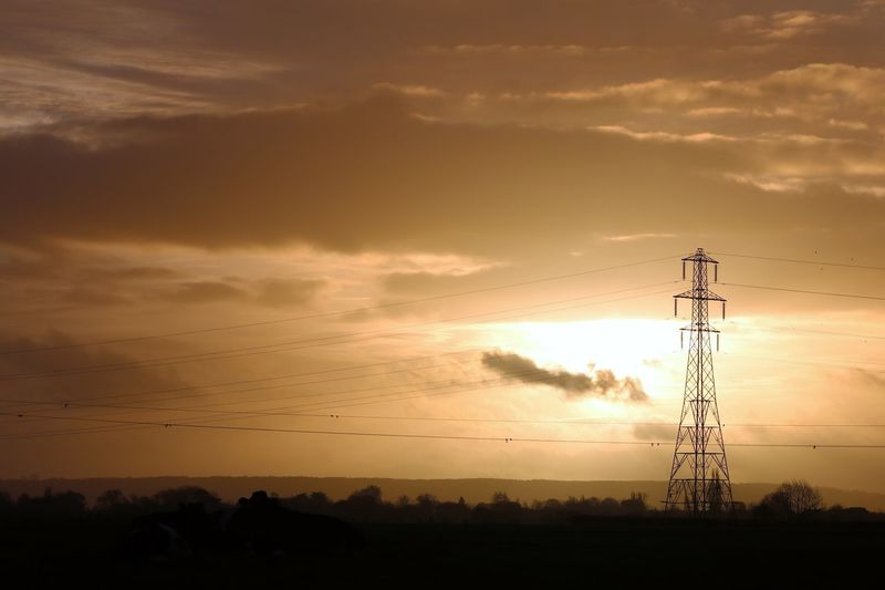 Electricity Pylon On Landscape Against Sky During Sunset