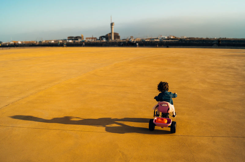 Rear View Of Girl Riding Tricycle On Playground Against Sky