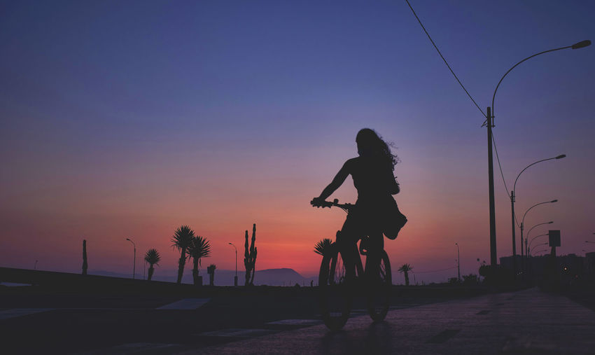 Silhouette woman jumping on street against sky during sunset