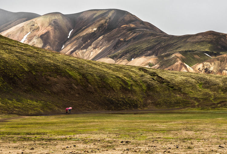 Man on golf course against mountains