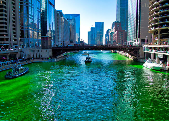 Police boat joins the crowd along the Chicago River, which is dyed green for St. Patrick's Day tradition. Chicago Chicago River Chicago Loop City Downtown Chicago Exterior Green Holiday St. Patrick's Day St. Patty's Day Tradition Boat Bridge - Man Made Structure Bridgehouse Building Colorful Crowded Dearborn Street Dyed Food Coloring Nautical Vessel People Plumbers Union Police Boat Shadows