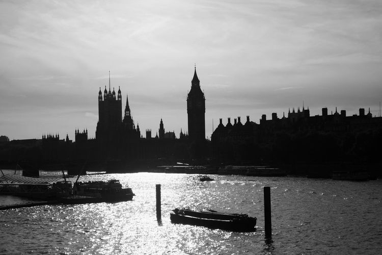 Big ben by thames river against sky in city
