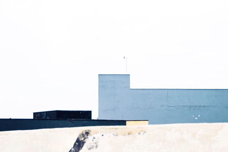 Backgrounds Minimalism Lines And Shapes Selective Focus Urban Landscape Urban Geometry Urban Geometric Shape Architecture Built Structure Building Exterior Copy Space Sky Building Clear Sky Day Wall - Building Feature Wall Outdoors Sunlight White Color Low Angle View Roof City Blue Cold Temperature Modern Background 17.62°