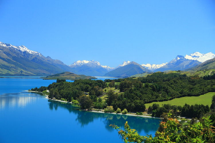 Scenic view of lake and mountains against clear blue sky
